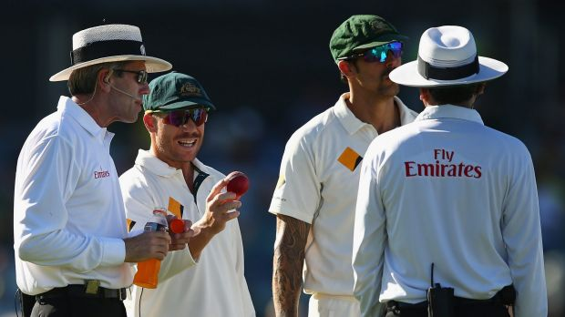 Not happy: David Warner speaks with he umpires over the condition of the ball.