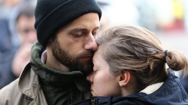 A couple embrace after laying flowers at the La Belle Equipe cafe in Paris France.