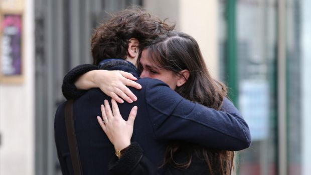 A couple embrace after laying flowers at the La Belle Equipe cafe in Paris on Saturday.