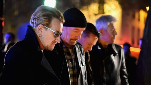 Bono and band members of U2 pay their respects and place flowers on the pavement near Bataclan Concert Hall.