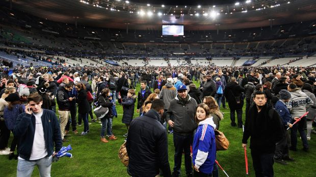 Terrified: Spectators gather on the pitch at Stade de France after news of the bombing and terrorist attacks reached the ...
