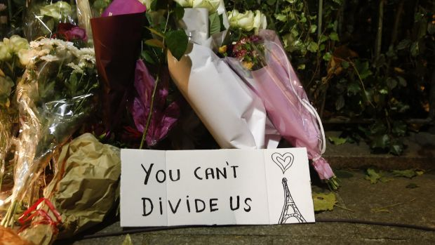 Flowers stand next to a sign near the Bataclan concert hall.