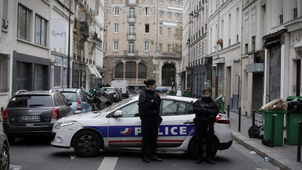 Police guard the crime scene near the La Belle Equipe cafe in Paris, France on Saturday.