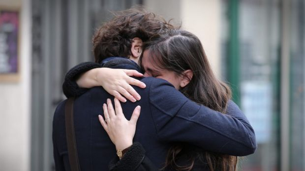 A couple embrace after laying flowers at the La Belle Equipe cafe on Saturday.