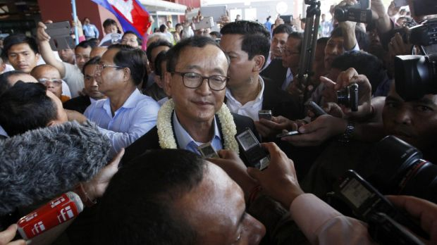 Cambodia's opposition leader Sam Rainsy, centre, faces arrest if he returns to his country as early as Monday