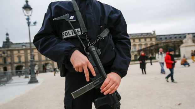 A police officer stands guard holding a gun at the Louvre museum in Paris, France, on Saturday.