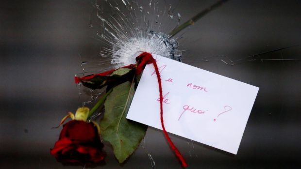 """A rose in a bullet hole with a note that translates to """"In the name of what?"""" at La Belle Equipe in Paris on Sunday."""
