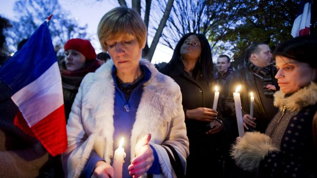 Alexandra Salomon, from Paris, France, centre, joins a vigil outside the White House in Washington DC.
