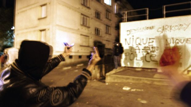 """Youths gesture next to a wall with graffiti  that reads """"F--- the police, Sarkozy resign"""", in the Renault housing ..."""