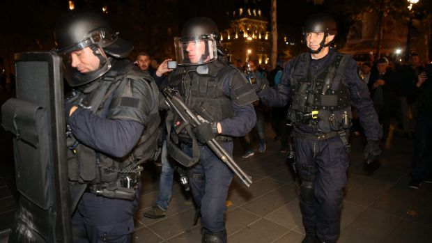 Police with a shotgun and a ballistics shield react to suspicious behaviour at Place de la Republique in Paris on ...