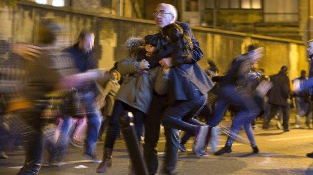 A man carries two children after panic broke out.