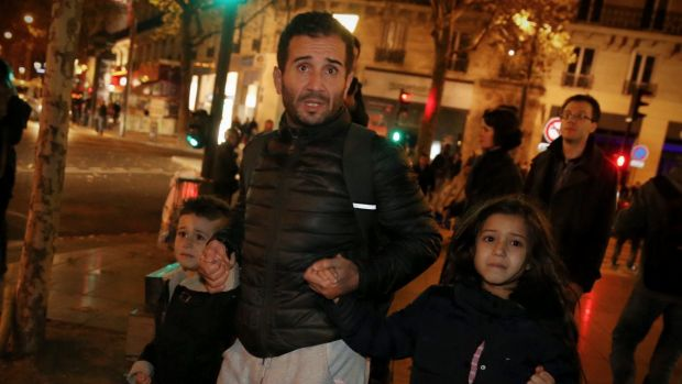 A father with his children leave Place de la Republique after crowds dispersed in a panic and police drew their weapons.