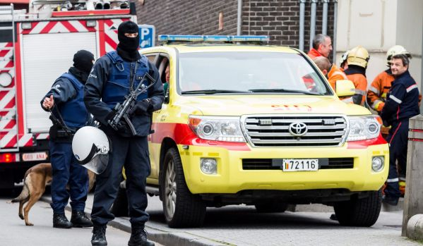 Armed police guard a street in the Brussels neighbourhood of Molenbeek amid a manhunt for a suspect of the Paris attacks.