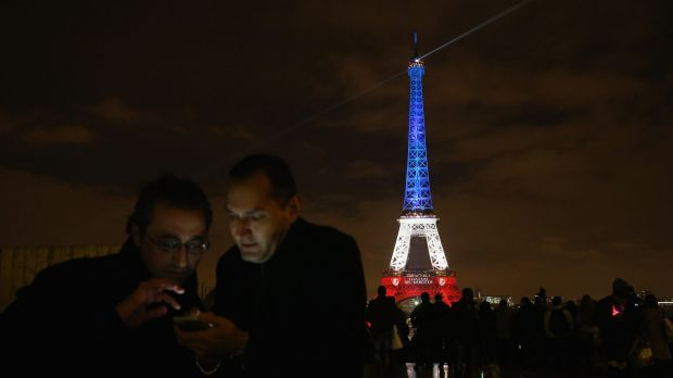 Parisians look at a mobile phone with the Eiffel Tower illuminated in red, white and blue in the background.