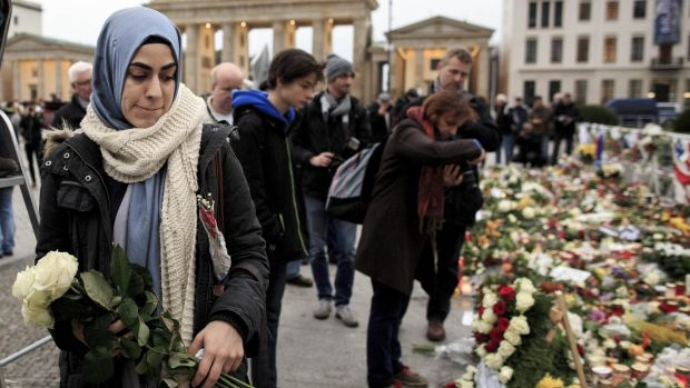A young woman holds white roses outside the French Embassy among candles, messages and flowers left by mourners ...