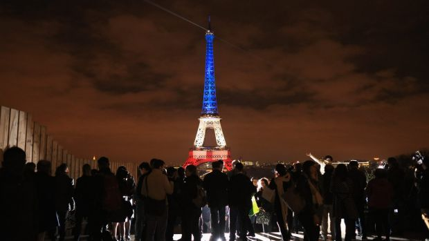 The Eiffel Tower is illuminated in the colours of the French flag.