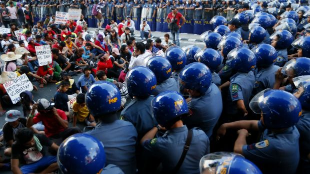 Security is tight in Manila as police confine a group of protesters along a street after attempting to march towards the ...