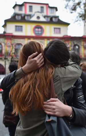 Two girls embrace opposite the main entrance of the Bataclan concert hall as French police lift the cordon.