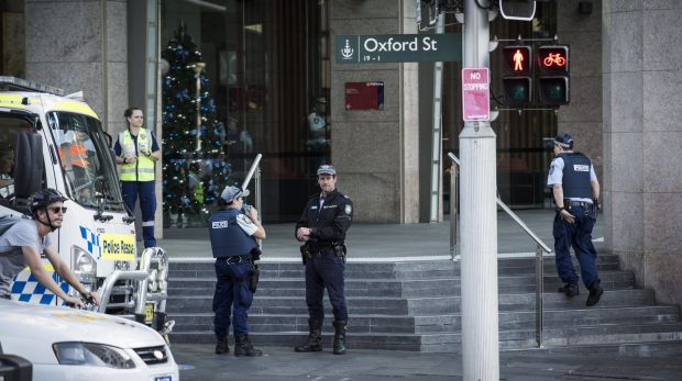 Police are seen inside and outside of a building on the corner of Wentworth avenue and Oxford street in Sydney.