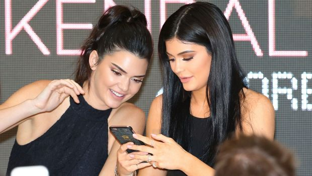 Kendall Jenner and Kylie Jenner look at their mobile phones as they arrive at Chadstone.