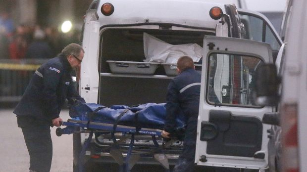 Two men carry a body into a hearse after the raid in Saint-Denis on Wednesday.
