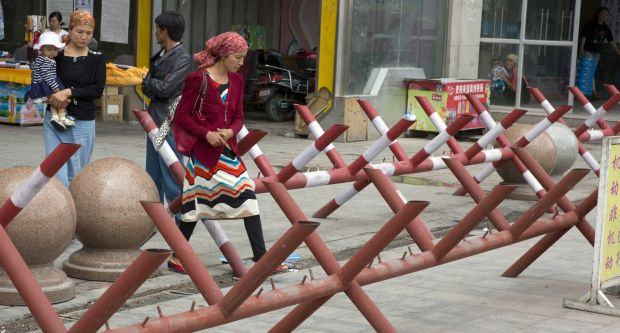 Uighur women walk past barricades set up at the entrance to a shopping district in the city of Aksu in western China's ...