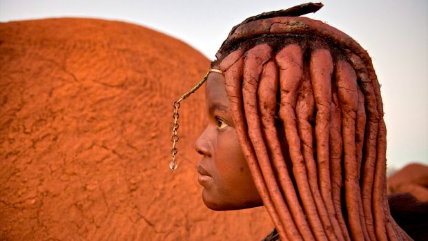 Women of Himba tribe have braids swept back in red plaits covered with Otjize, a mixture of butterfat and ochre.