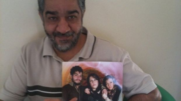 Late Iranian asylum seeker Ali Rahimi, with a photograph of his family. Mr Rahimi died at Villawood detention centre of ...