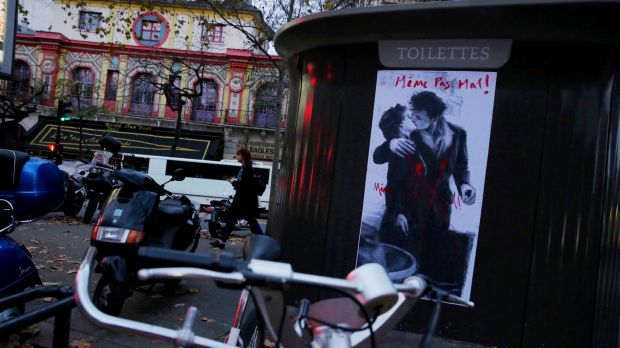 """A poster of wounded lovers stating """"Not even hurt"""" opposite the Bataclan concert hall."""