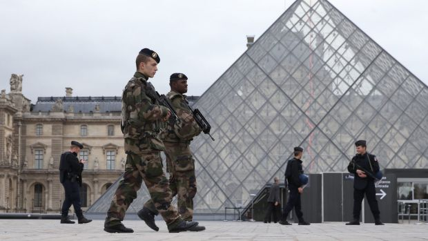 French military patrol the Louvre in Paris, which reopened on Monday.