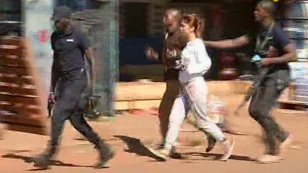 A woman is led away by security from the Radisson Blu Hotel in Mali.