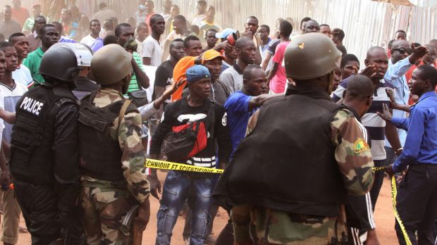 Mali troops try to control a crowd of onlookers near the Radisson Blu hotel, after Islamic extremists armed with guns ...