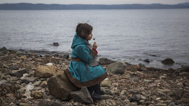 A Syrian girl eats a lollipop after her arrival on a small boat from the Turkish coast on the Greek island of Lesbos on ...