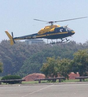 A helicopter lifts off in hazy conditions on Saturday at the Sea World car park. Emergency services are battling a fire ...