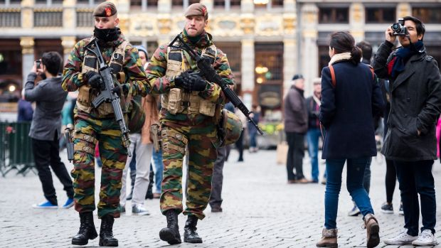 Belgian Army soldiers patrol in the picturesque Grand Place in the centre Brussels. An international manhunt for ...