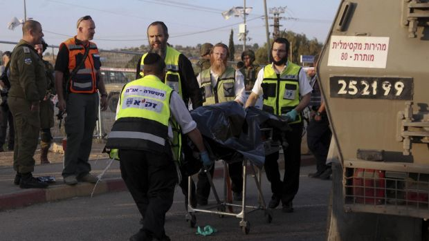 Israeli emergency services evacuate the body of a Palestinian from the scene of an attack near the West Bank Gush Etzion ...