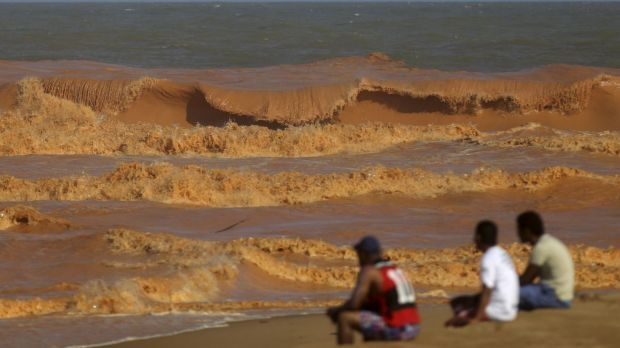 People watch the sea on the coast of Espirito Santo, Brazil, last week after mud from the tailings dam arrived 600 ...