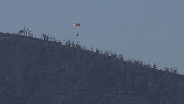 A pilot parachutes out of the warplane which went down in Syria's north-western Turkmen town of Bayirbucak. .
