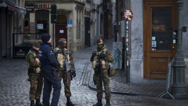A police officer and armed soldiers stand guard at Grand Place square in Brussels, Belgium, on Monday as the search for ...