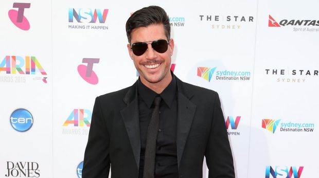 The Bachelor Sam Wood showed off the fruits of his gym labour in a suave black Calibre suit and added some black rimmed ...