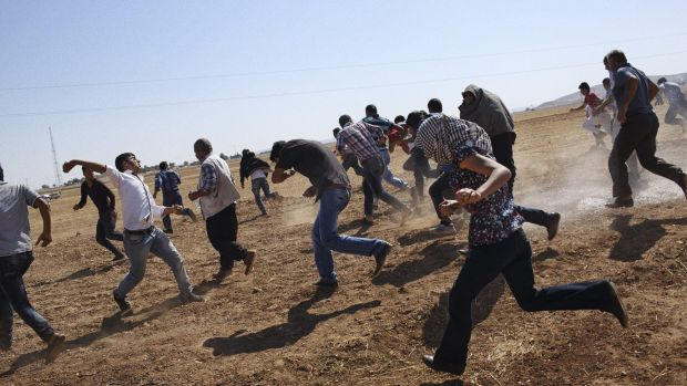 Kurdish protesters at the border with Syria flee from Turkish teargas after trying to watch the fighting in the border ...
