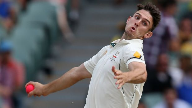 Pinkish hue: Mitchell Marsh bowls sends one down during the first day-night Test.