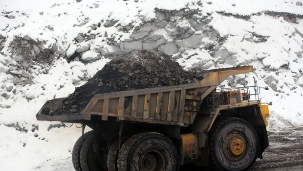 A dump truck transports coal along a snow covered road in Russia.
