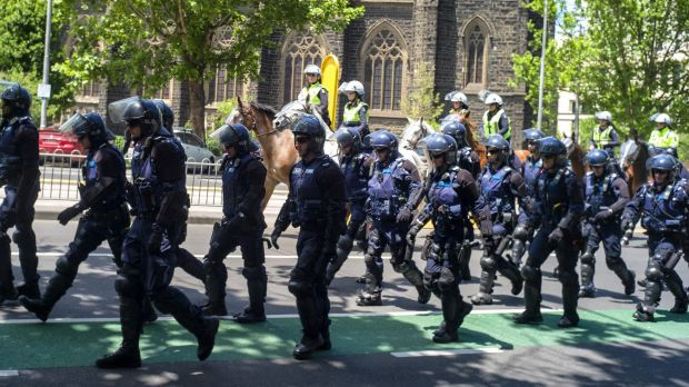 Police officers move towards State Parliament for the rally.