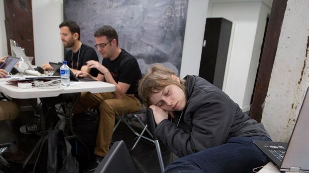 Sarah Erlington sleeps after working on her project all night at the NAB Hackathon in Sydney in November, while Juliius ...