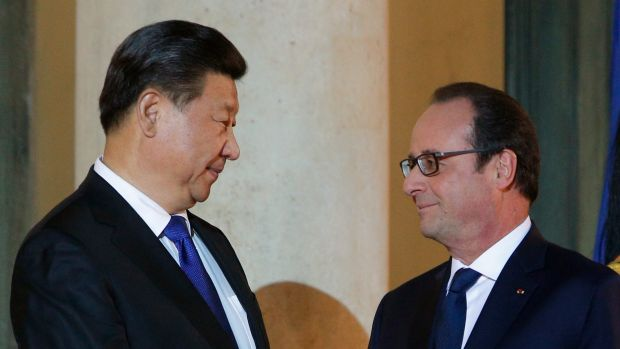 France's President Francois Hollande welcomes Chinese President Xi Jinping prior to a working dinner before the start of ...