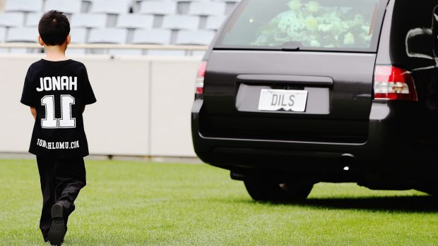 Jonah and Nadene's son Dhyreille Lomu follows the hearse as it departs the Public Memorial for Jonah Lomu.