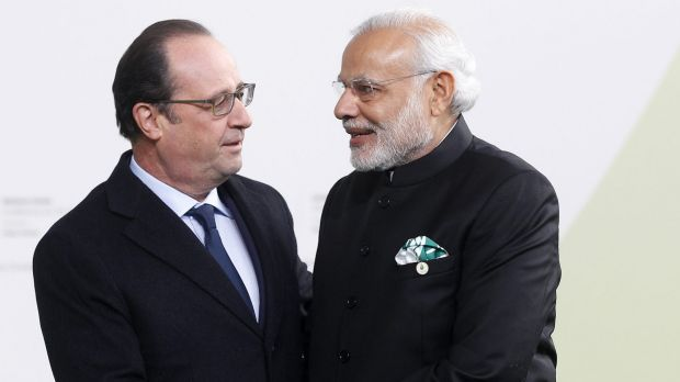 French President Francois Hollande shakes hands with Indian Prime Minister Narendra Modi as he arrives at the climate ...