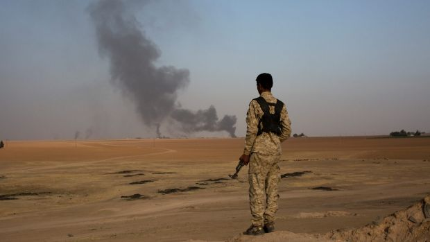 A member of an Arab tribal militia fighting the Islamic State group watches as smoke rises from a crude oil refinery in ...