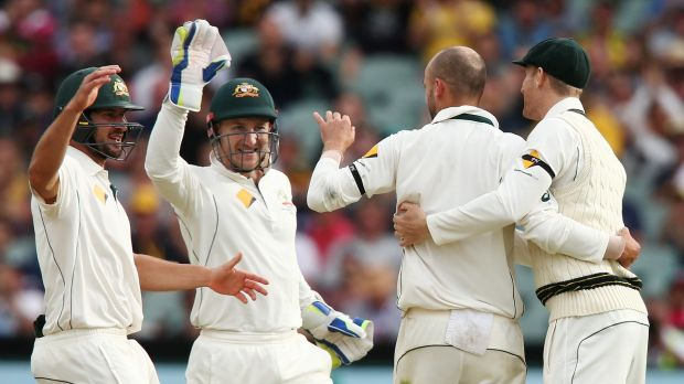 Team first: Joe Burns and Peter Nevill celebrate with Nathan Lyon after he took the wicket of Mark Craig.